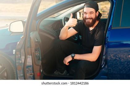 Foto von fröhlichem Bärenmann, der in seinem neuen Auto sitzt und Daumen zeigt