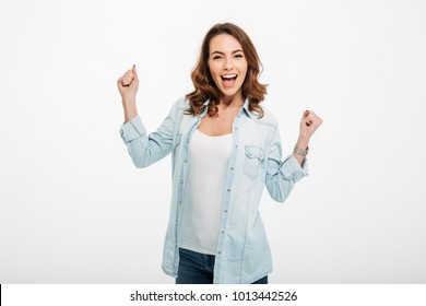 Photo of cheerful beautiful young woman standing isolated over white wall background. Looking camera showing winner gesture.