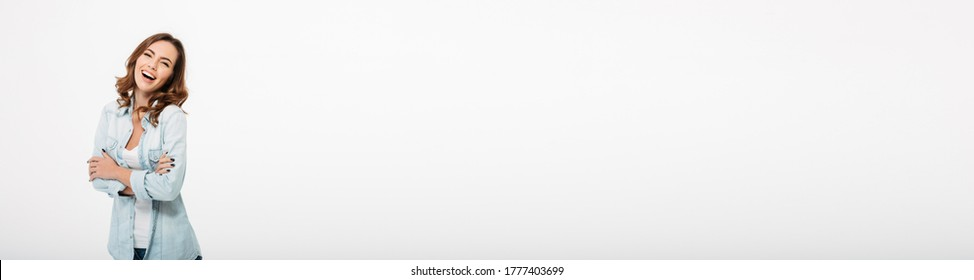 Photo of cheerful beautiful young woman standing isolated over white wall background. Looking camera.