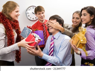Photo of cheerful businesswoman keeping her hands on man?s eyes while their colleagues preparing gifts for him