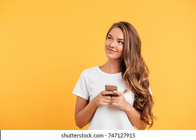 Photo of cheerful cute beautiful young woman chatting by mobile phone isolated over yellow wall background. Looking aside.