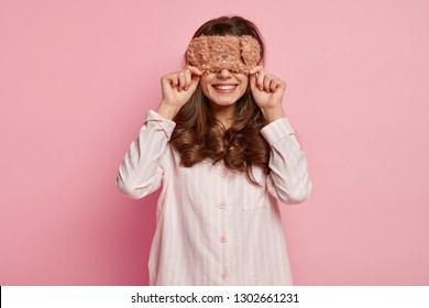 Photo cheerful dark haired woman with curly hair, covers eyes with warm eyemask, wears casual pyjamas, smiles gently, waits for surprise from husband in morning, isolated over pink background