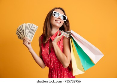 Photo of cheerful elegant young woman in sunglasses and red dress holding fan of money and colorful shopping bags, looking aside, isolated on yellow background