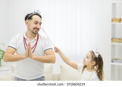 Photo of cheerful father and daughter holding wand while wearing costumes.