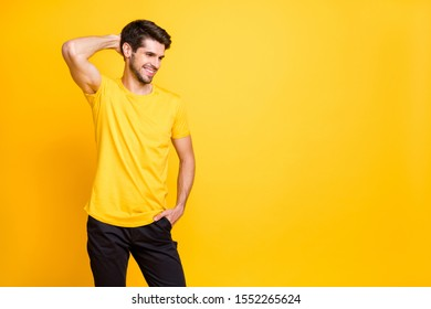 Photo of cheerful handsome attractive man having fun relax resting smiling toothily beaming wearing black trousers yellow t-shirt isolated over yellow vivid color background