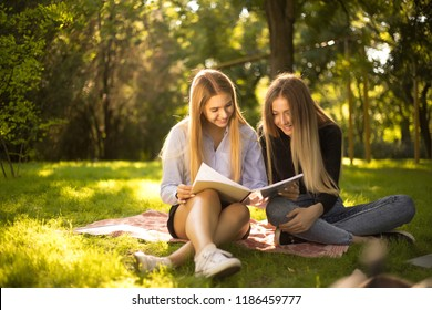 Photo of cheerful happy young beautiful ladies students sitting in the park outdoors on grass holding copybook doing homework.