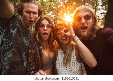 Photo of cheerful hippies men and women smiling and taking selfie in forest