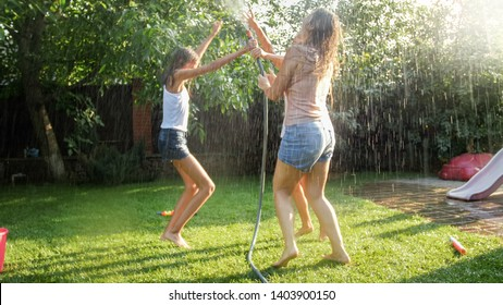 Photo of cheerful laughing girls in wet clothes dancing in the garden and holding water hose. Family playing and having fun outdoors at summer
