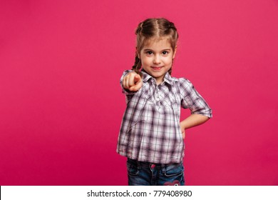Photo of cheerful little girl child standing isolated over pink background. Looking camera pointing to you.