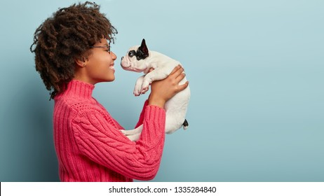Photo of cheerful loving female stands sideways, holds little white puppy near face, teases and wants to kiss, has spare time, demonstrates good care, isolated over blue wall with copy space