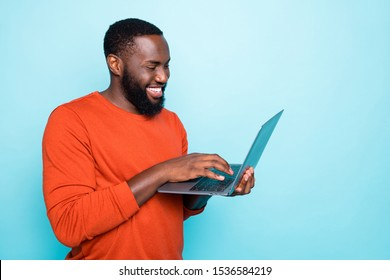 Photo of cheerful man browsing through his laptop smiling toothily making new video which can be watched on his social media isolated vivid blue color background