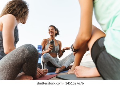 Photo of cheerful multiethnic sportswomen in tracksuits smiling and talking while sitting on yoga mats by seaside in morning