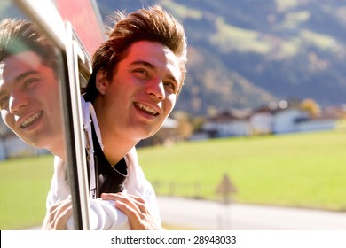 Photo of cheerful passenger looking out of train window while moving fast