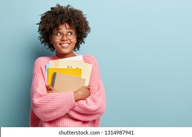 Photo of cheerful pleased schoolgirl looks upwards, dreams about recieving degree, carries papers and notepad, dressed in oversized pink jumper, isolated over blue background with copy space