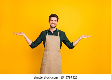 Photo of cheerful positive attractive kind friendly coffee maker showing you to kinds of one sort object of coffee smiling toothily wearing apron isolated over yellow vivid color background