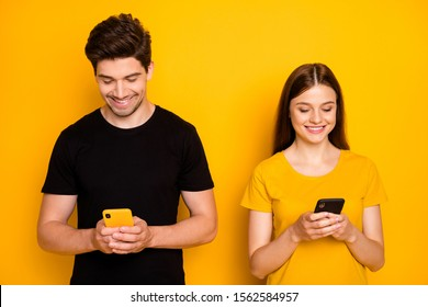 Photo of cheerful positive cute nice addicted people browsing through their telephones chatting with each other despite standing side by side isolated vivid shiny color background in black t-shirt