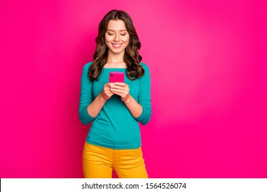 Photo of cheerful positive girlfriend browsing through smartphone smiling toothily reading feednews isolated pink vivid color background