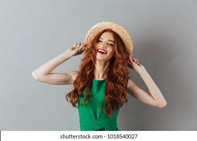 Photo of cheerful redhead young woman in green dress and hat standing over grey wall background. Looking camera.