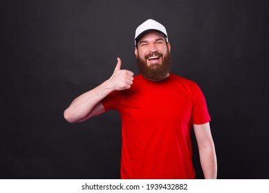 Photo of cheerful smiling young man in red t-shirt showing thumb up over black background.
