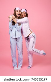 Photo of cheerful two girls friends in pajamas isolated over pink background. Looking camera showing peace gesture.