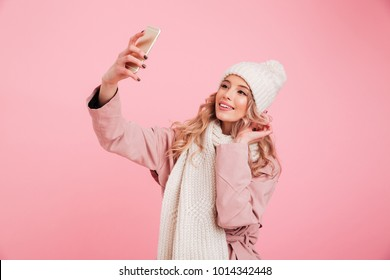 Photo of cheerful woman standing isolated over pink background wearing warm scarf. Looking aside take a selfie by mobile phone.