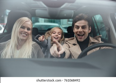 Photo of cheerful young man sitting in car with his wife and daughter. Looking aside and pointing.