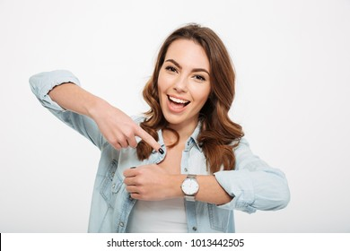 Photo of cheerful young woman isolated over white wall background. Looking camera showing her watch on the hand.