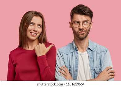 Photo of cheerful young woman points with thumb at hesitant boyfriend, suggests asks him about what happened, stand together against pink studio wall. Look at my displeased uncertain best friend