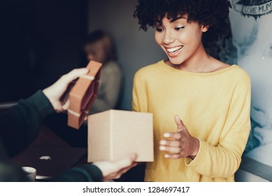 Photo of cheerful young woman with smile looking in present box. Man opening gift to surprising her lady