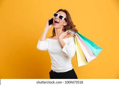 Photo of cheerful young woman standing isolated over yellow background holding shopping bags. Looking aside talking by mobile phone.