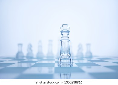 Photo of chess king standing in checkerboard front of the same colour set in bright background.