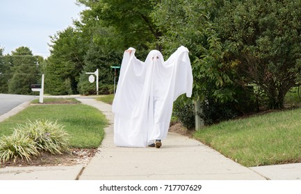 A photo of a child in a ghost costume creeping down the sidewalk toward you.