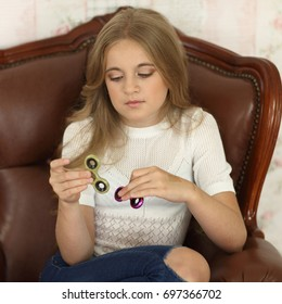 photo of a child with green and pink fidget spinners in hands, sitting in leather chair, wearing white shirt and jeans