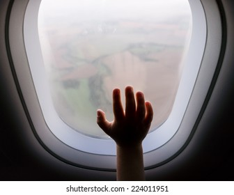 photo of child hand on a aeroplane vindow