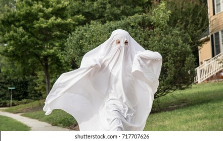 A photo of a child running down the side walk in a ghost costume.