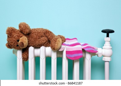 Photo of a childs teddy bear and woolen mittens drying on an old traditional cast iron radiator, good image for winter and childhood themes. The bear is a generic non-brand bear, FYI he's called Bob!