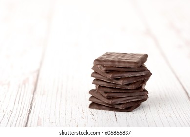 Photo of chocolate bar on white wooden table