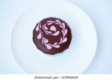 A photo of chocolate cupcake with topping on white plate isolated on white background, close up