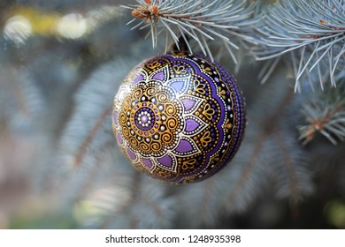 Photo of christmas ball with sunflower mandala painted manually. New Year decoration.