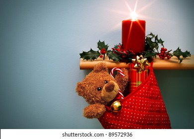 Photo of a Christmas stocking filled with presents and a candle surrounded by holly, the star from the flame was done in camera. The teddy is generic and is not a brand name bear. Copy space on left.