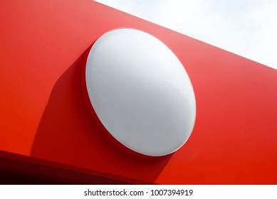 Photo of circle empty signboard isolated on red background. Template isolated on red background. For graphic designers presentations and portfolios white round mock-up with new sign.