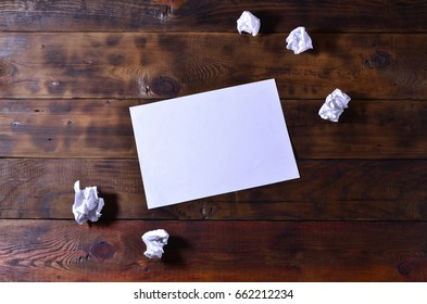 Photo of a clean white blank sheet of paper lie on a brown wooden background. Plenty of space for text