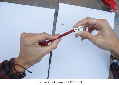 Photo of close up of a hands pulling a pencil point to continue writing on a table.
