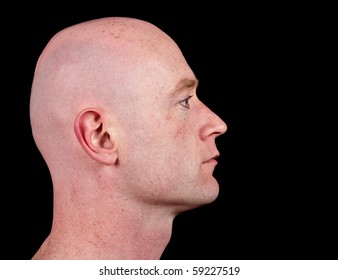 photo close up picture of a male head from side on black. bald shaved head face close up portrait profile.