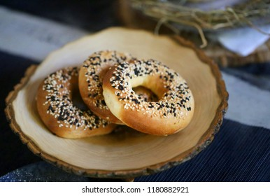 Photo of a close-up bagels with poppy seeds on a wooden stand
