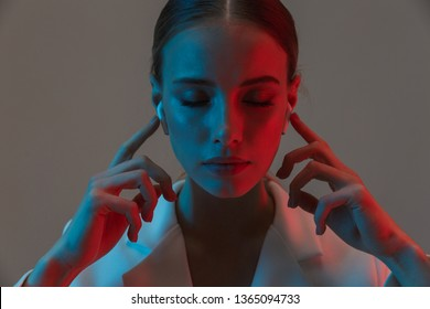 Photo closeup of elegant woman 20s wearing earpods looking at camera while standing under neon lights isolated over gray background