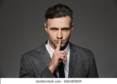 Photo closeup of executive director man wearing classic costume looking on camera and holding index finger on lips isolated over gray background