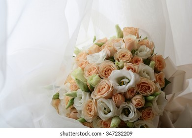 Photo closeup front view ball-shaped elegant wedding bouquet of fresh pastel pink white roses flowers buds with ribbons for bridal ceremony on white curtain lace background, horizontal picture