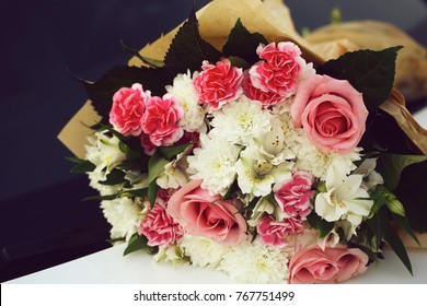 Photo closeup front view elegant colorful bouquet of fresh pink white roses chrysanthemum flowers green leaves in plain florist paper packaging on grey indoor background, horizontal picture