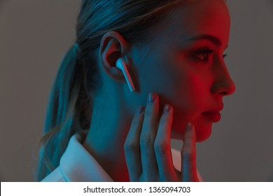 Photo closeup of gorgeous woman 20s wearing earpods looking at camera while standing under neon lights isolated over gray background
